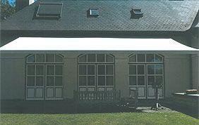 store solaire extérieur avec façade et jardin grisés.