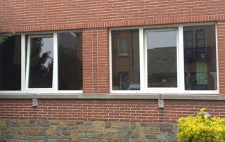 fenêtres en PVC blanc sur façade rouge