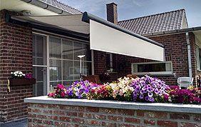 Store banne avec petite retombée, en arrière-plan d'un bac à fleurs coloré.