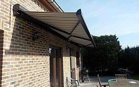 maison en brique équipée d'une toile solaire extérieure à l'entrée