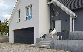 petite maison blanche avec porte de garage vert foncé
