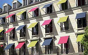 façade avec nombreuses fenêtres surplombées de toiles solaires multicolores