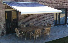 façade dotée d'un voile d'ombrage et terrasse meublée.