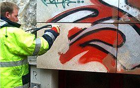 homme nettoyant des tags rouges et noirs