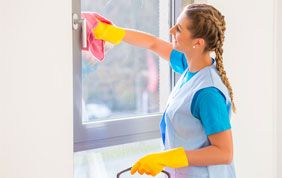 femme de ménage lavant une vitre