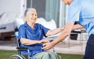 dame en fauteuil roulant avec aide soignante