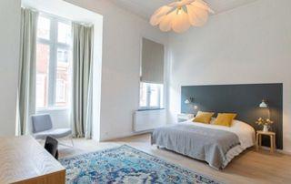 chambre à coucher avec longues tentures gris clair