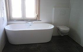 baignoire devant la fenêtre dans une salle de bain