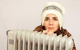 femme qui a froid cachée derrière un radiateur