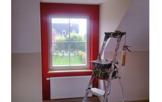 échelle et matériel de peinture devant mur et radiateur