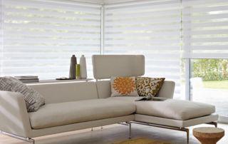 canapé beige dans salon avec stores tissu blanc
