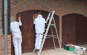 Peintres occupés à peindre une porte de garage