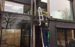 Agent d'entretien qui nettoie des vitres en hauteur