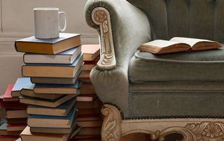 pile de vieux livres à côté d'un fauteuil ancien