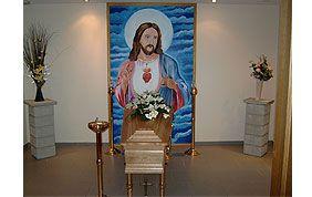 Christ représenté sur le mur derrière un cercueil
