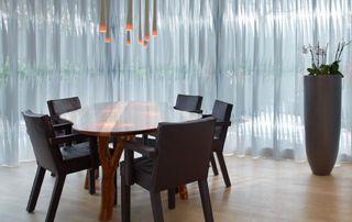 Salle à manger avec fins voilages transparents aux fenêtres