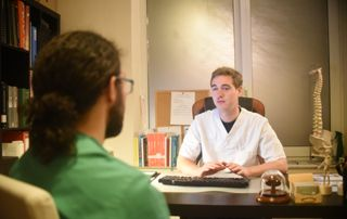 Ostéopathe en consultation avec patient
