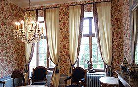 rideaux crème dans pièce tapissée à haut plafond
