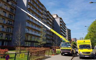 Lift sur camionnette jaune devant immeuble
