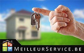 main tenant une clé avec une maison floue en fond