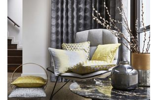 fauteuil avec coussins tissus devant tenture à motifs gris clair et gris foncé
