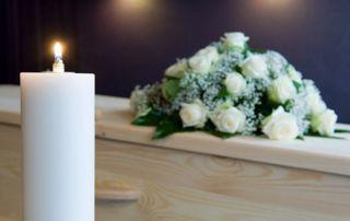 bougie, cercueil et couronne mortuaire