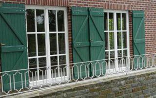 volets vert fonc et châssis blancs sur mur en briques rouges