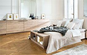 chambre à coucher avec lit en bois et grand meuble de rangement assorti