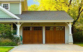 grandes portes battantes en bois avec allée de garage