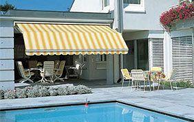 marquise rayée jaune et blanc sur terrasse avec piscine