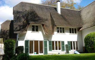 maison avec toit en chaume : murs peints en blanc et volets en vert