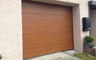 porte de garage en bois sur mur en crépi beige