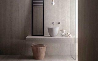 Pièce de vie avec table et grande baie vitrée et carrelage gris effet béton