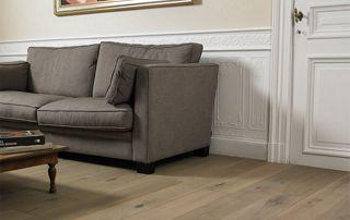 Salon avec plancher en bois et fauteuil gris