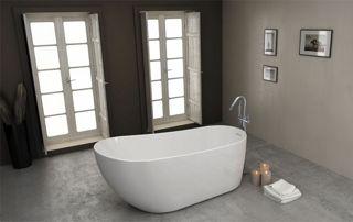 Salle de bain avec sol en béton ciré, baignoire centrale et portes fenêtres