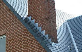 cheminée sur toit incliné en ardoises