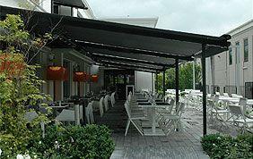 tente solaire qui surplombe une terrasse meublée