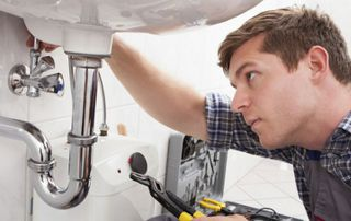 plombier réparant un lavabo
