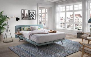 Lit sur pied avec matelas et surmatelas dans une chambre blanche et bleu clair