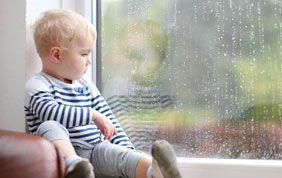 Jeune enfant assis sur le rebord d'une fenêtre
