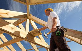 ouvrier qui pose une charpente en bois