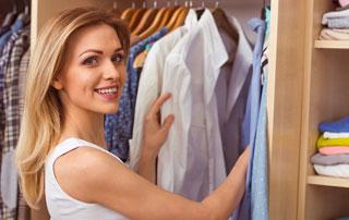 Femme qui range ses vêtements dans son dressing