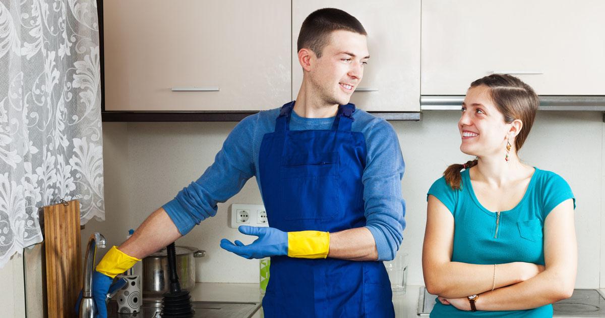 Femme qui accueille un plombier pour qu'il effectue des réparations sanitaires