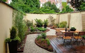 terrasse en bois, allée en pierres et meubles de jardin en bois