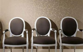 trois chaises brunes devant un mur beige