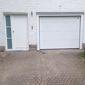 porte de garage blanche à côté d'une porte d'entrée