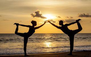 couple qui fait du yoga sur la plage