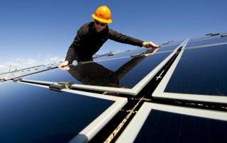 photo d'un homme plaçant un panneau solaire