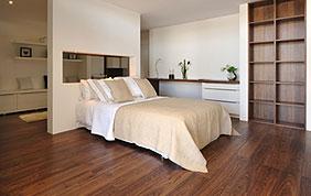 Chambre à coucher avec literie, parquet en bois foncé et étagère sur mesure