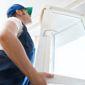 Homme en blue de travail qui remplace une fenêtre